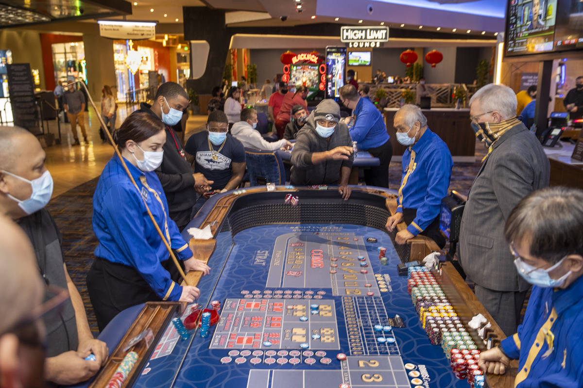 A craps table is busy with gamblers and croupier as casino floors have moved up to 35% occupanc ...
