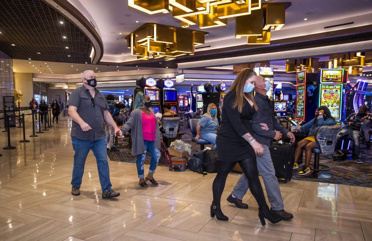 Couples pass by slot machines and the front desk area as casino floors have moved up to 35% occ ...