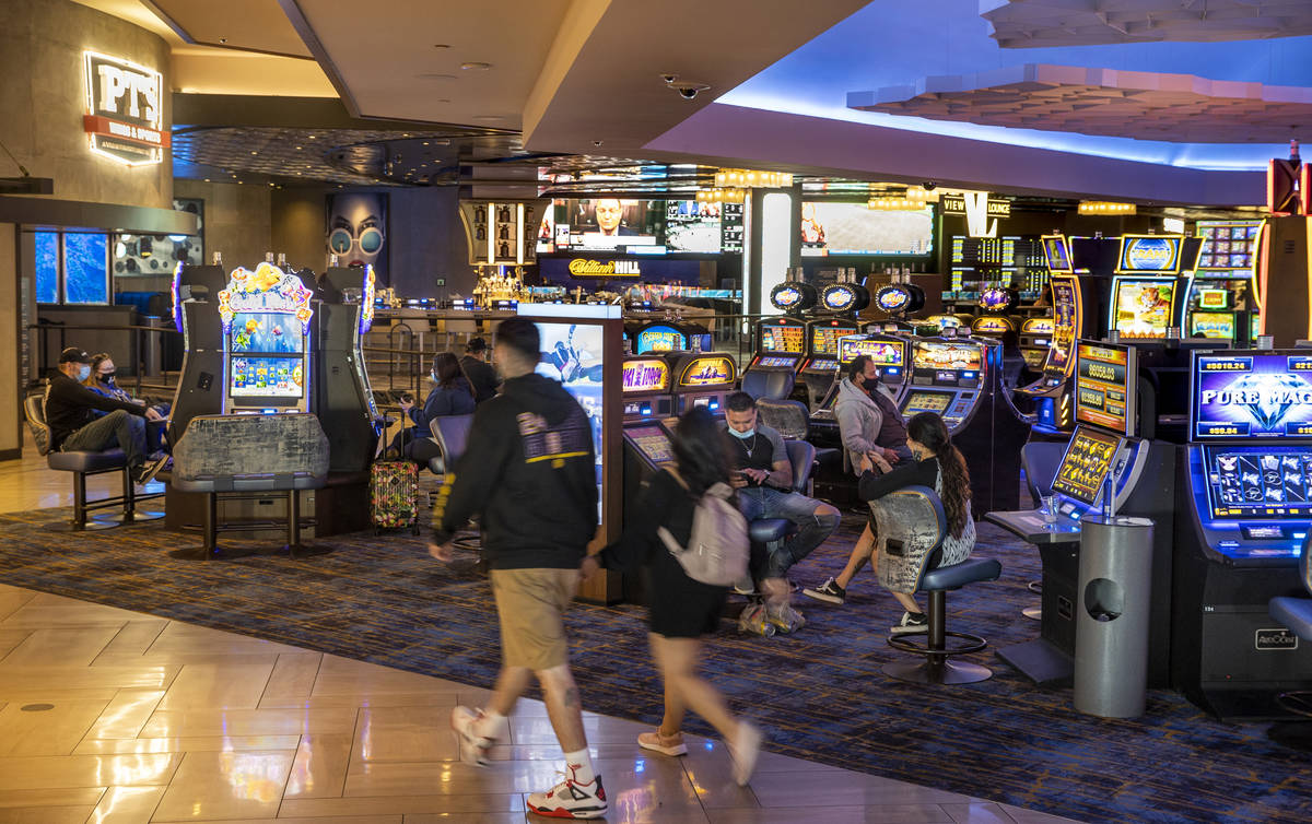 A couple walks through the slots area near the entrance to The Strat as casino floors have move ...