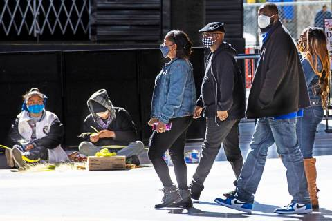 People wearing face masks, including cloth and KN95 style ones, walk along the Fremont Street E ...