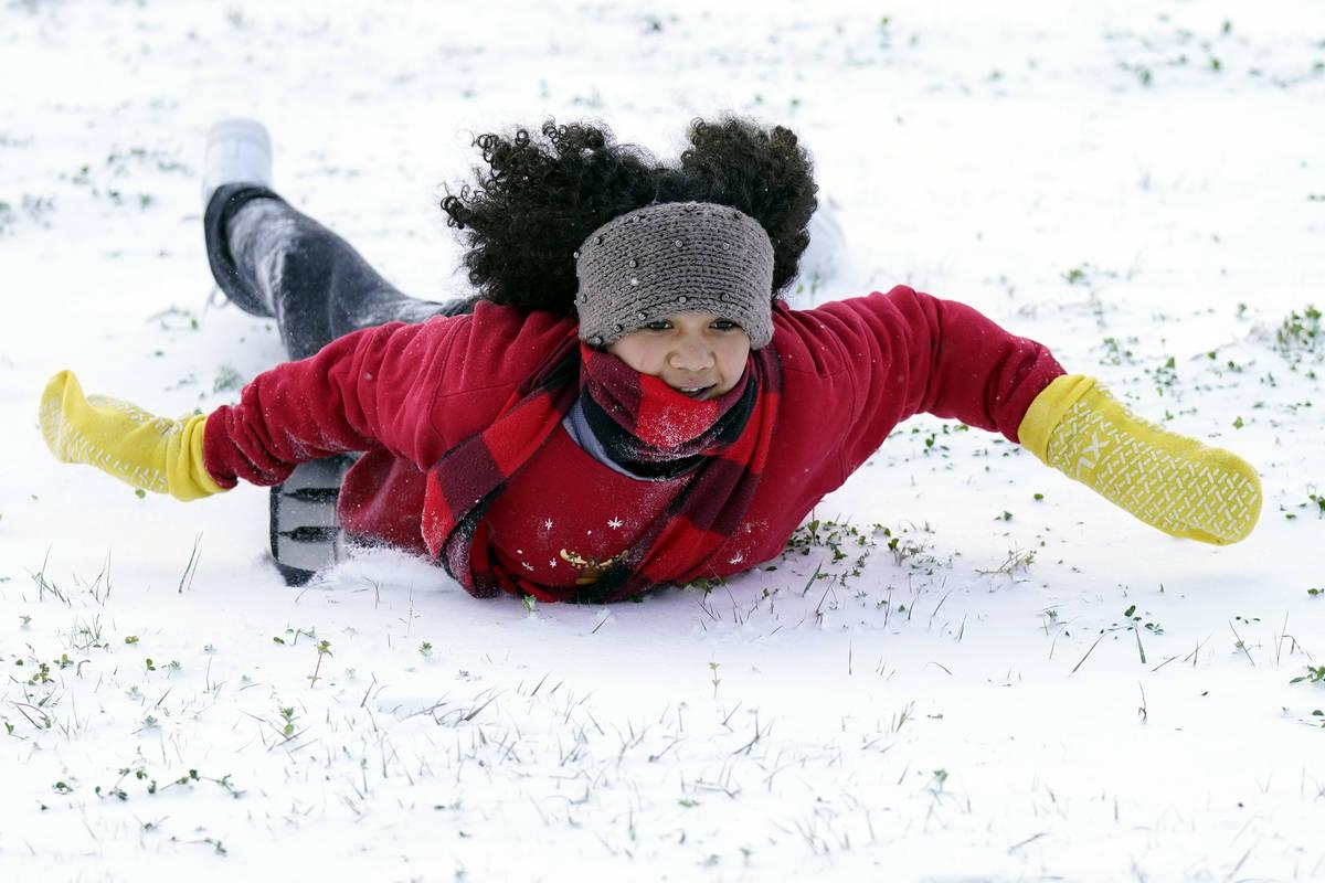 Alyssa Remi, 12, slides down a snow covered hill Monday, Feb. 15, 2021, in Houston.A winter sto ...
