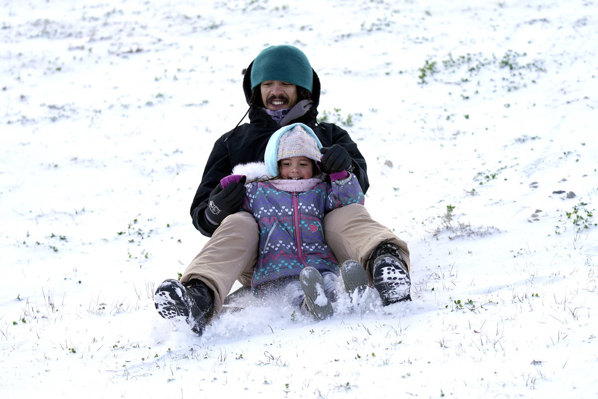 Robert Savannah and his daughter Sophia, 4, slide down a snow covered hill Monday, Feb. 15, 202 ...