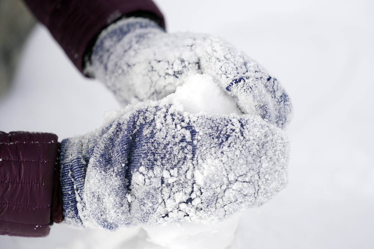 Cristina Lucero's hands are covered in snow while building a snowman Monday, Feb. 15, 2021, in ...