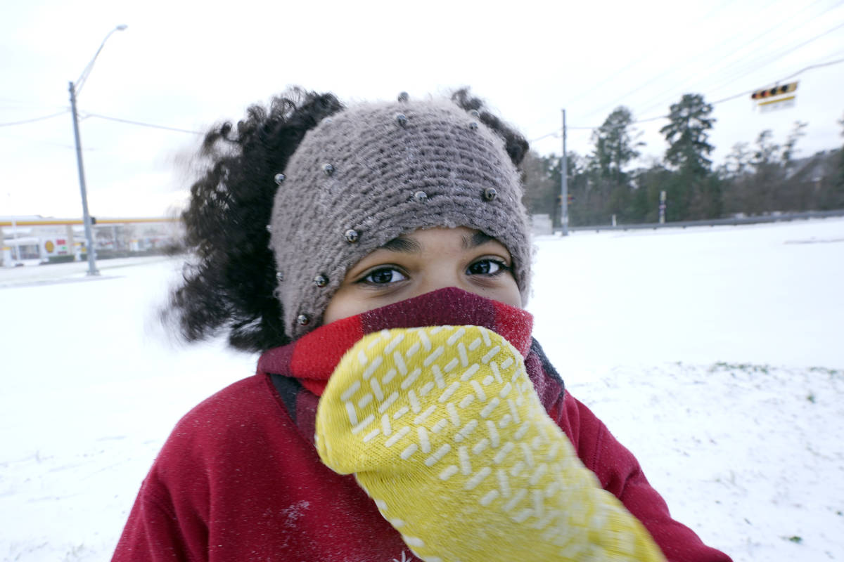 Alyssa Remi, 12, tries to keep warm while playing in the snow Monday, Feb. 15, 2021, in Houston ...