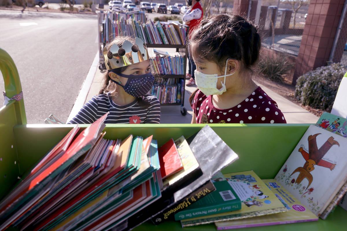 Amaliya Yusupova, 7, and Maiyah Concepcion, 8, choose books during a school supply distribution ...
