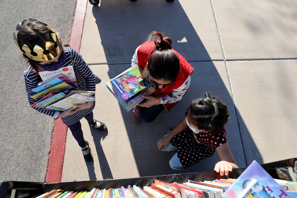 Amaliya Yusupova, 7, from left, her mother Pari Yusupova and Maiyah Concepcion, 8, choose books ...