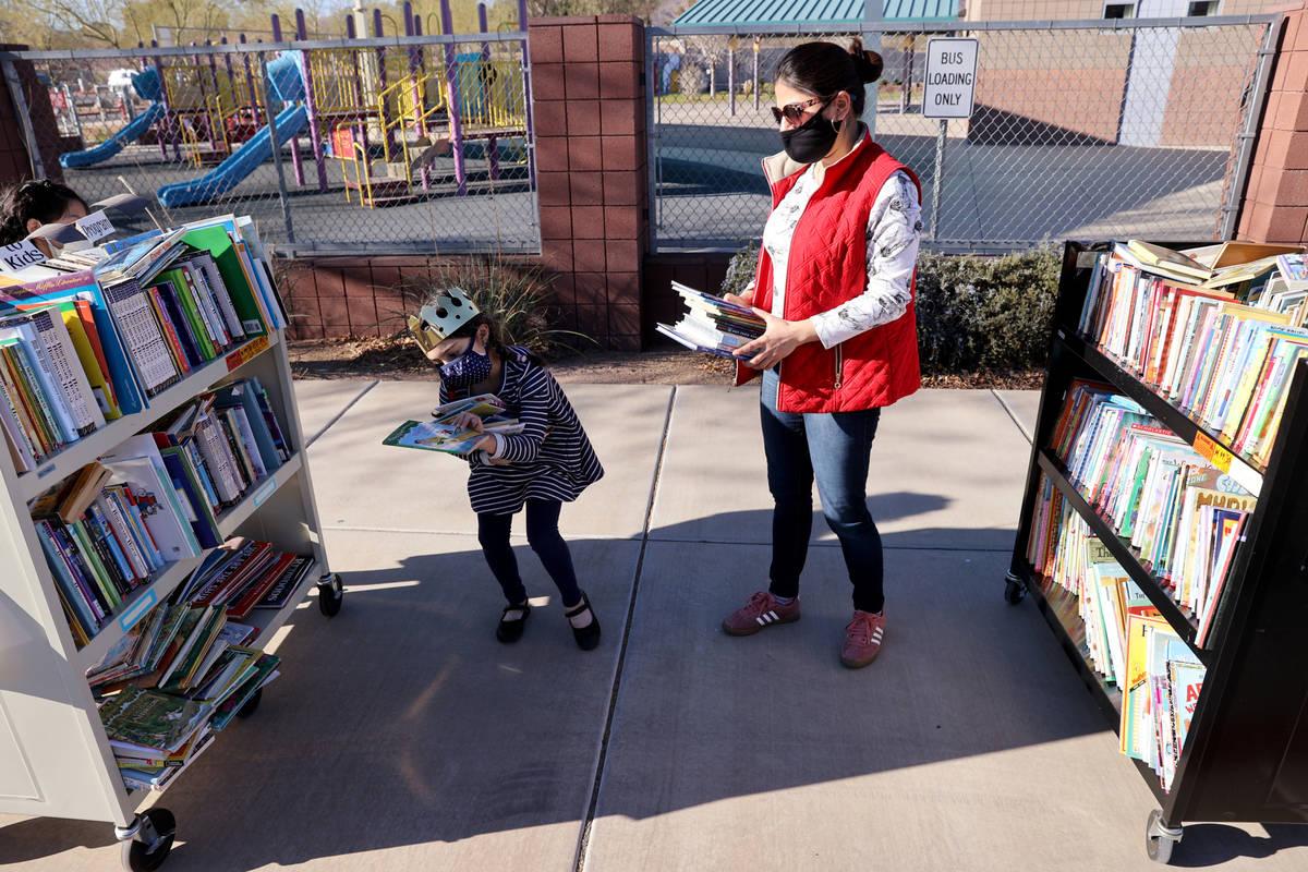 Amaliya Yusupova, 7, and her mother Pari Yusupova choose books during a school supply distribut ...