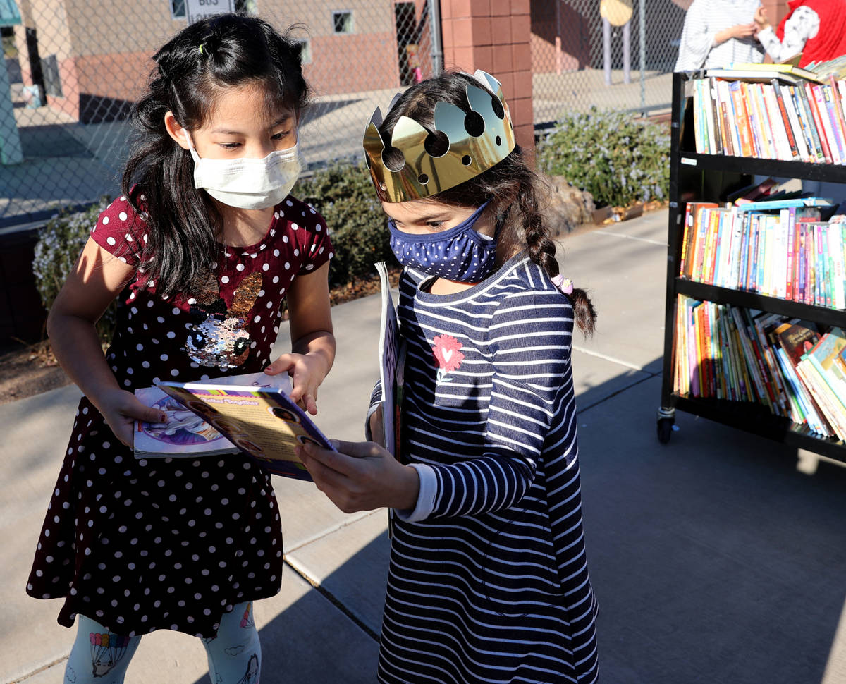 Maiyah Concepcion, 8, left, and Amaliya Yusupova, 7, choose books during a school supply distri ...