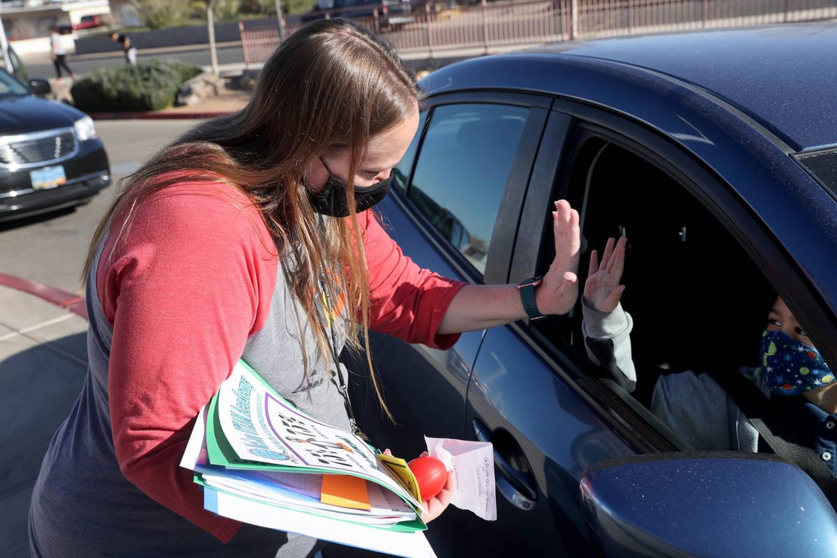 """First grade teacher Jessica Colgate does an """"air high-five"""" with third grader Aiden B ..."""