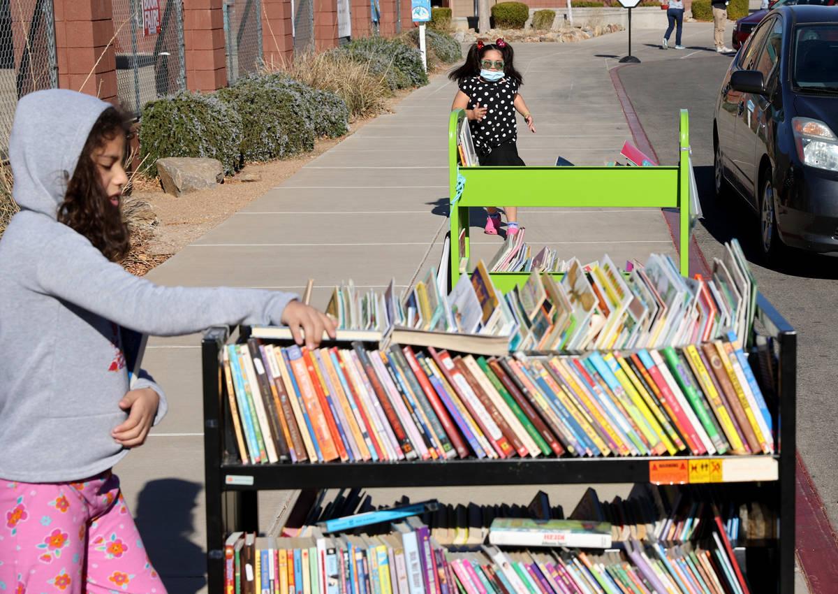 Second grader Thelma Castro-Rodriguez, 8, chooses books as first grader Tatiana Melgoza, 6, run ...