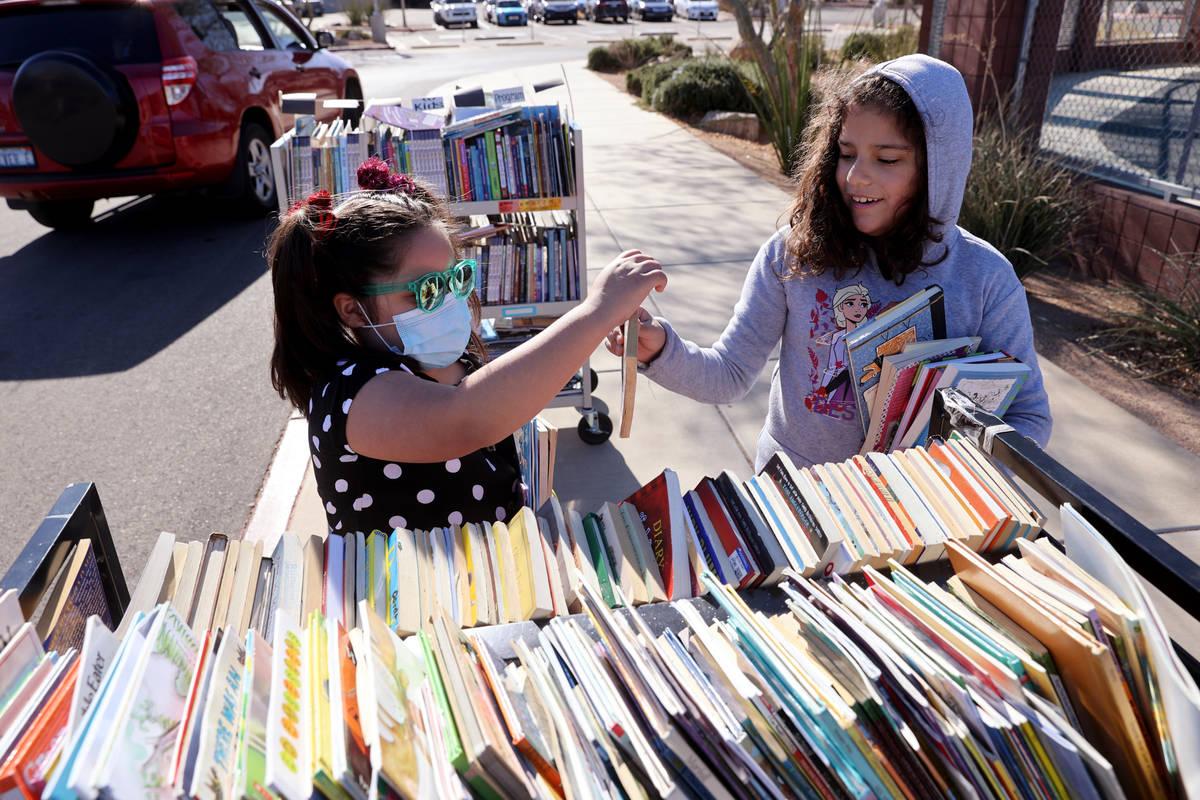 First grader Tatiana Melgoza, 6, left, and second grader Thelma Castro-Rodriguez, 8, choose boo ...