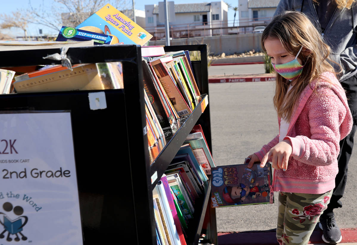 Kindergartner Olive Cantey, 6, chooses books during a school supply distribution event at McCaw ...
