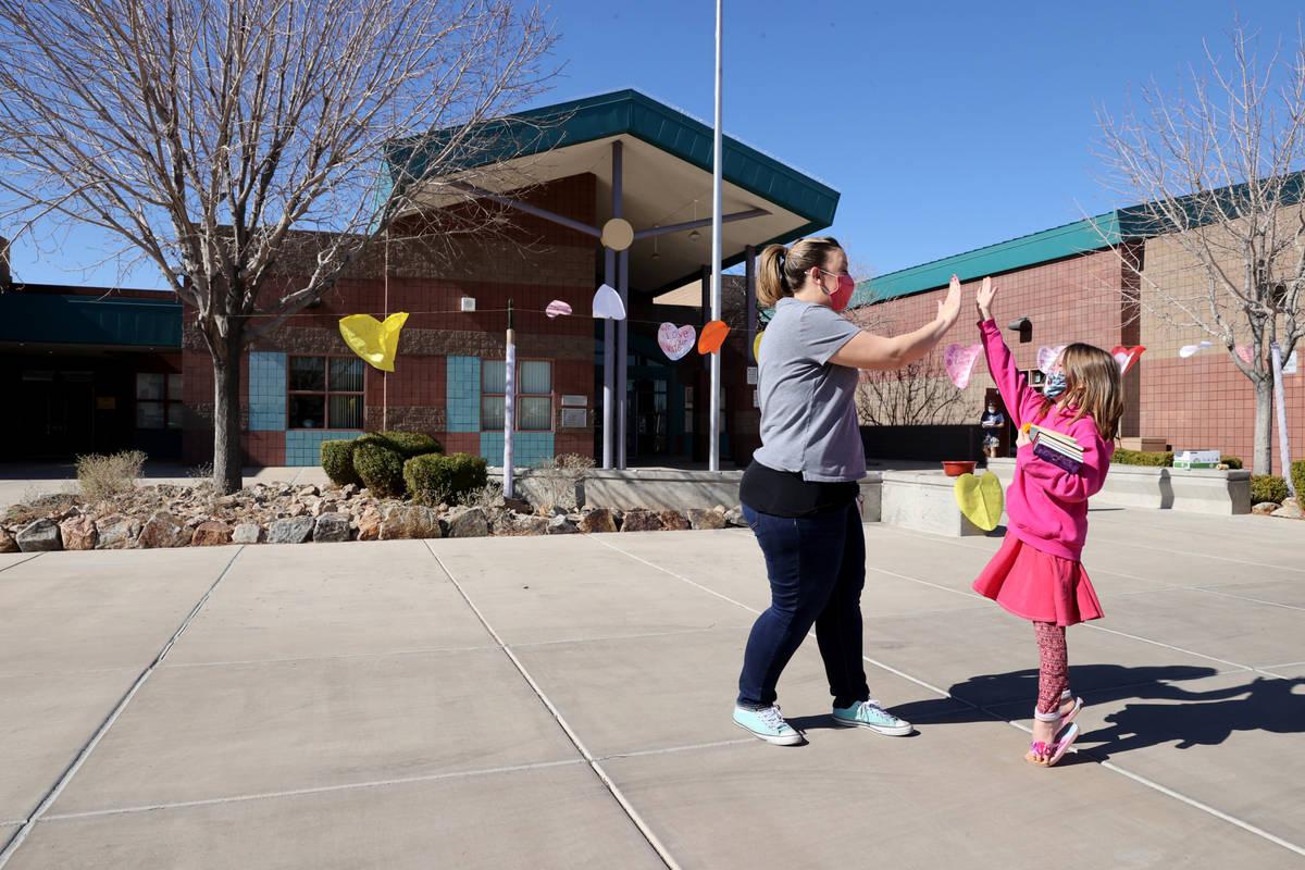 """Kindergarten teacher Molly Wood gives an """"air high-five"""" to first grader Caiome Macka ..."""