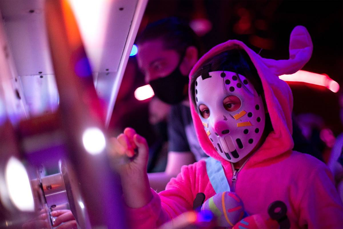 Jonate Spiewak, 7, wearing a Fortnite mask, intereacts with the art installation during opening ...