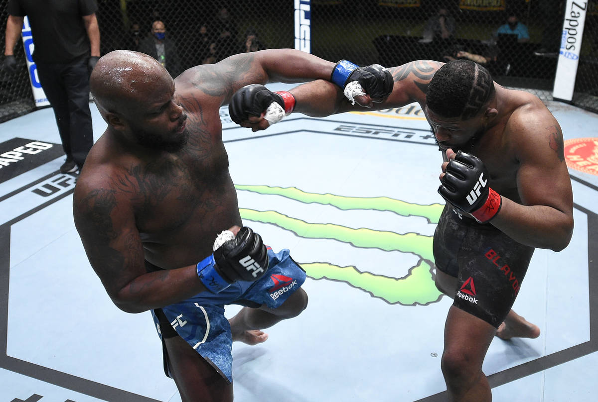 (L-R) Derrick Lewis and Curtis Blaydes trade punches in a heavyweight bout during the UFC Fight ...
