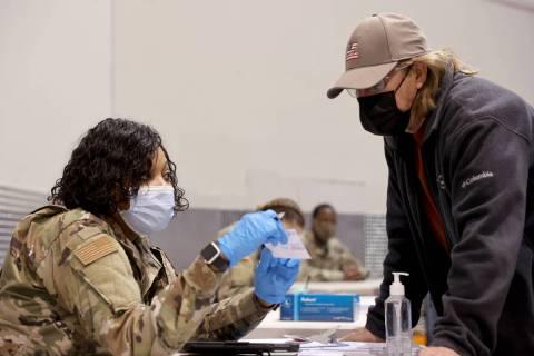 Mike Lucas, 70, of Henderson, checks in with Nevada National Guard Senior Airman Traesha Glover ...