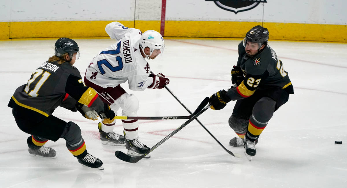 Colorado Avalanche right wing Joonas Donskoi, center, drives between Vegas Golden Knights cente ...