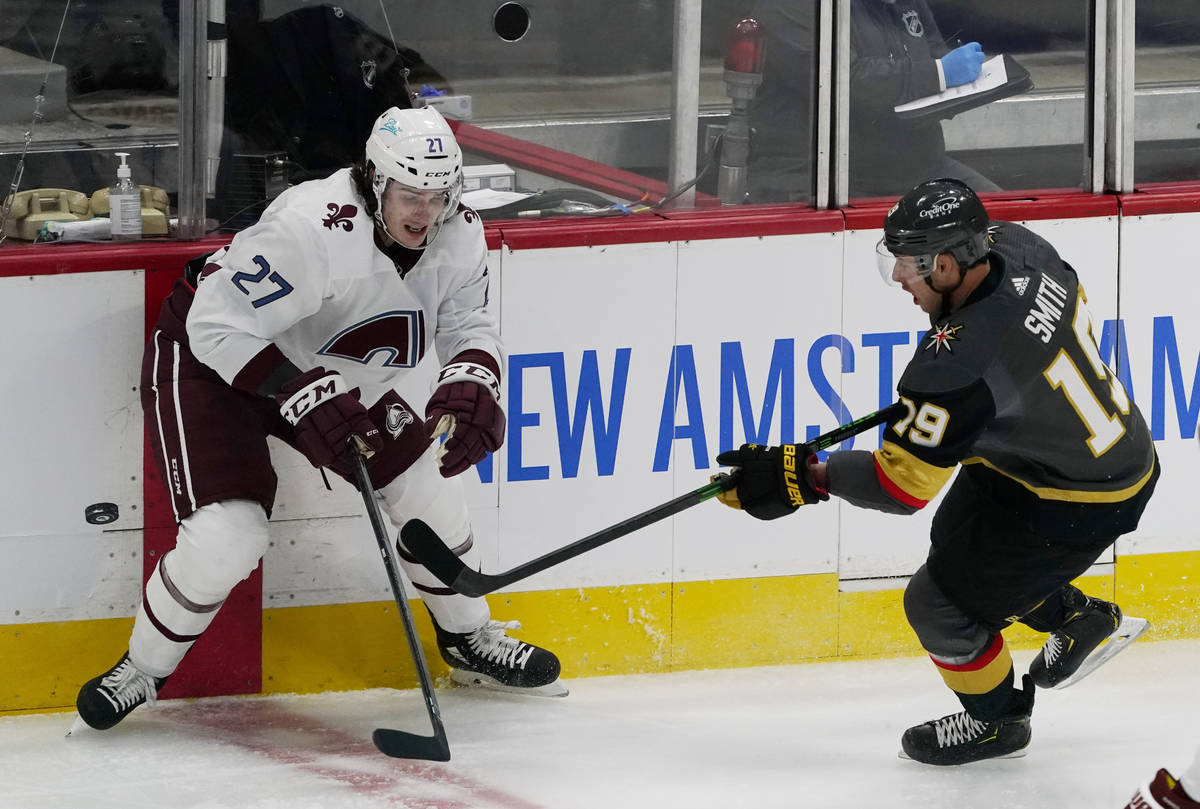 Vegas Golden Knights right wing Reilly Smith, right, passes the puck as Colorado Avalanche defe ...