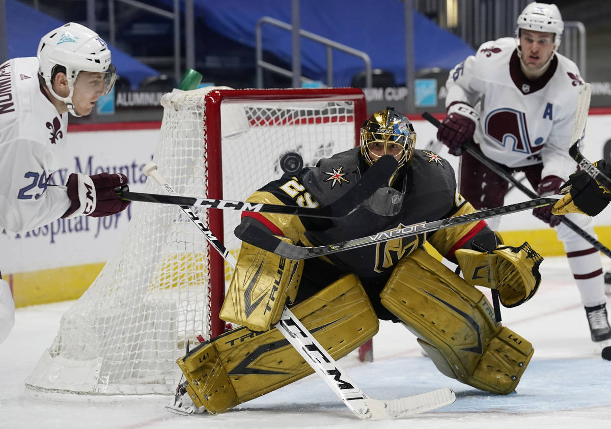 Colorado Avalanche center Nathan MacKinnon, left, swings at the puck as Vegas Golden Knights go ...