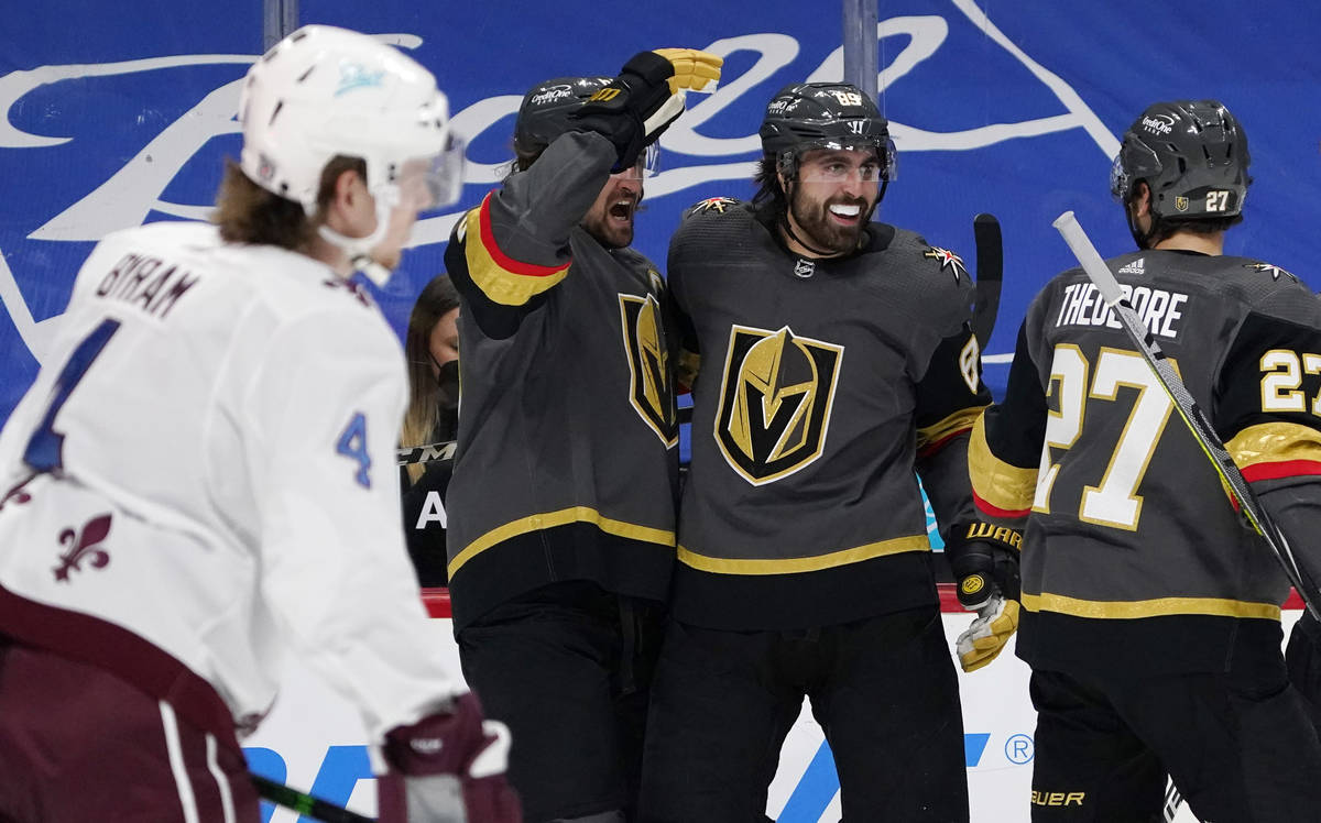 Vegas Golden Knights right wing Alex Tuch, back center, celebrates his goal with right wing Mar ...