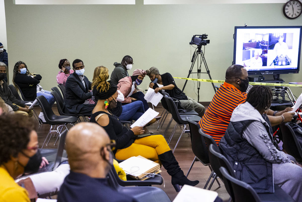 Attendees examine the agenda items at a Southern Nevada Regional Housing Authority board meetin ...