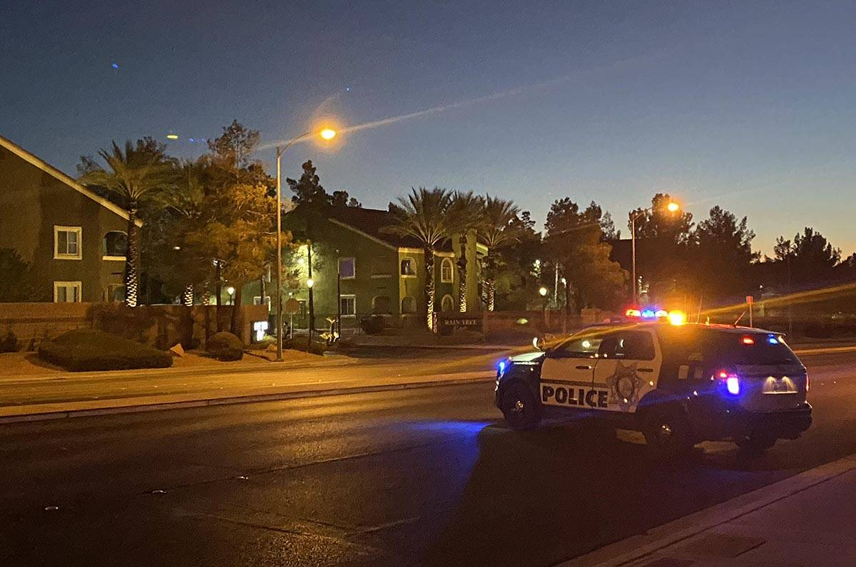 A police unit blocks a road as officers respond to a report of a woman with a hatchet in a cond ...