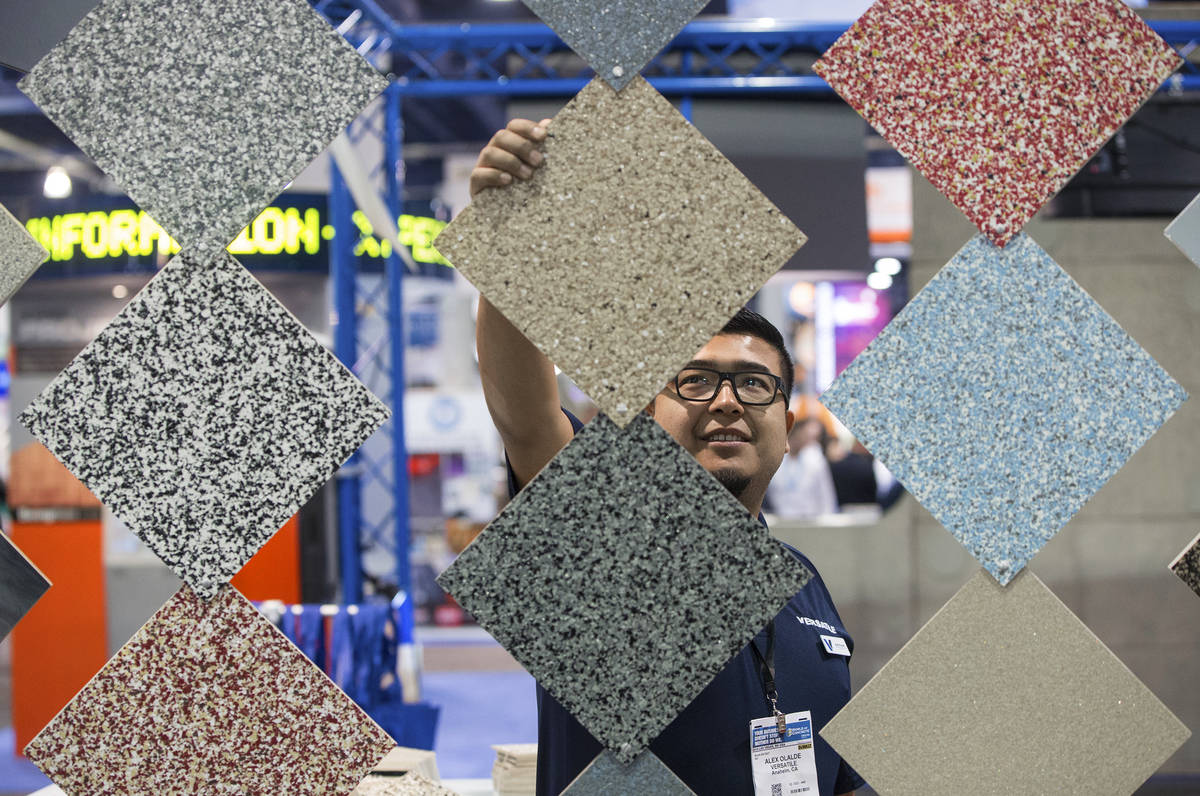 Alex Olalde, a sales representative with Versatile, straightens tiles at his booth during day t ...
