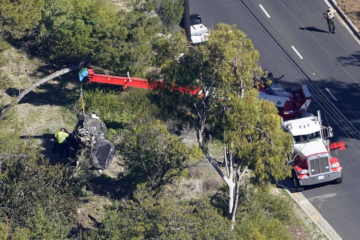 A crane is used to lift a vehicle following a rollover accident involving golfer Tiger Woods, T ...