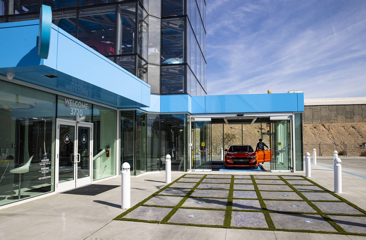 Bryce Bergevin, a vending machine specialist at Carvana, opens the door to a 2019 Chevrolet Cam ...