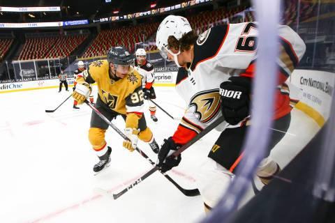 Golden Knights left wing Tomas Nosek (92) and Anaheim Ducks center Rickard Rakell (67) battle f ...