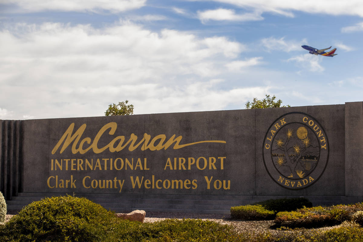 Sign for McCarran International Airport with plane taking off above at Tropicana Avenue and Kov ...