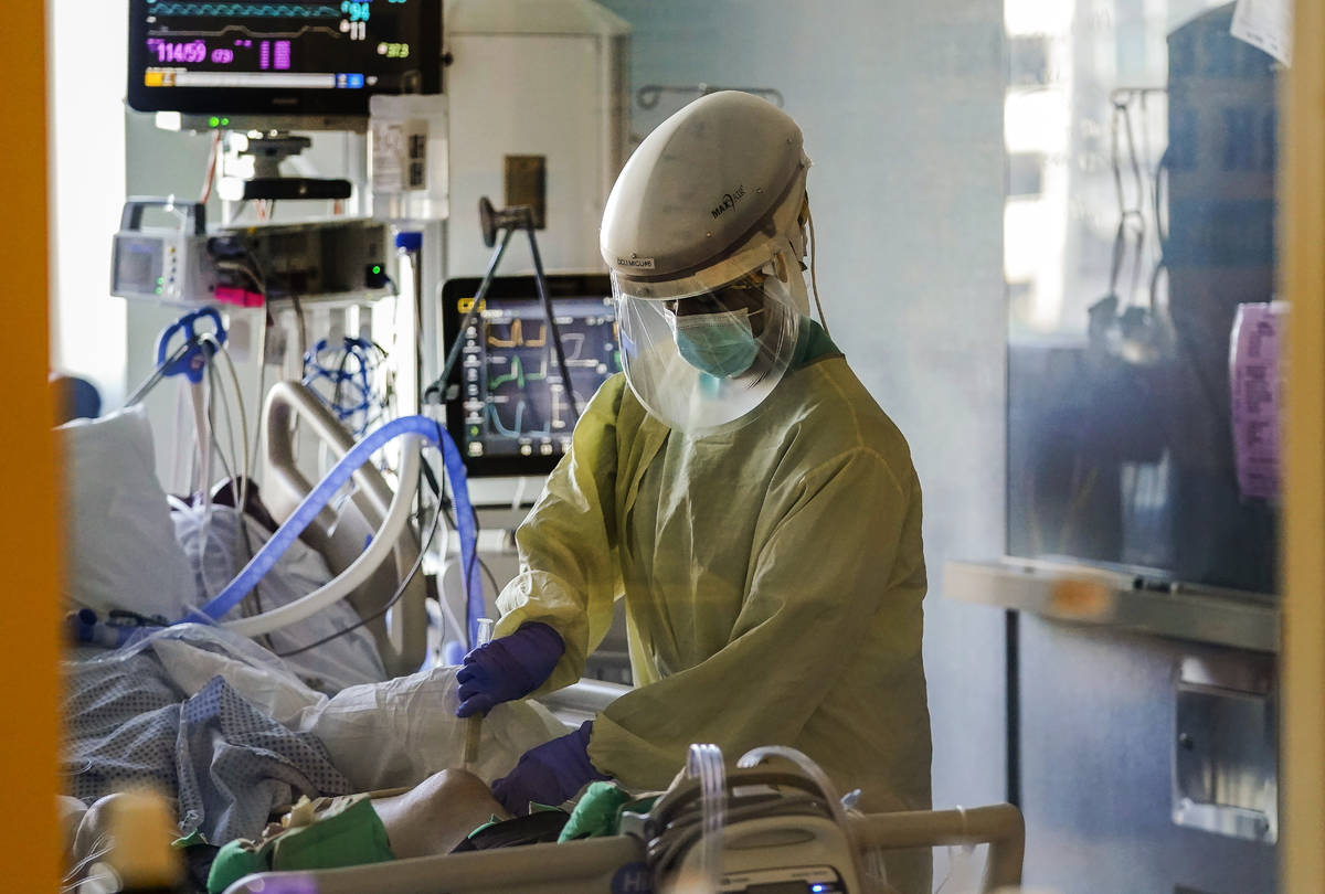 FILE - In this Wednesday, Jan. 13, 2021 file photo, a healthcare worker tends to a COVID-19 pat ...