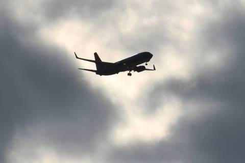 A Sun Country Airlines plane flies under cloudy sky as it approaches McCarran International Air ...