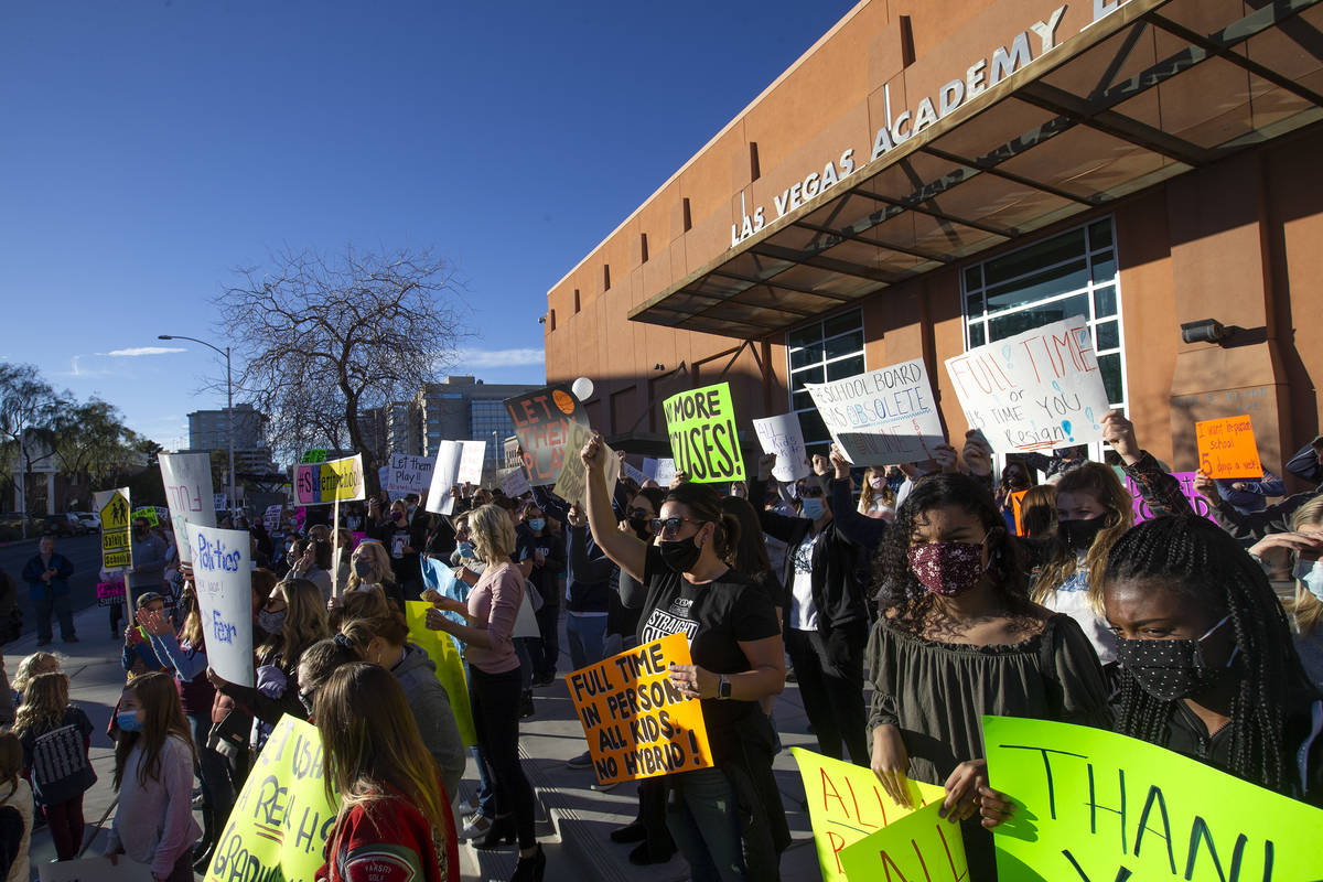 A group of parents, students and folks who want kids back in school protest before outside Las ...