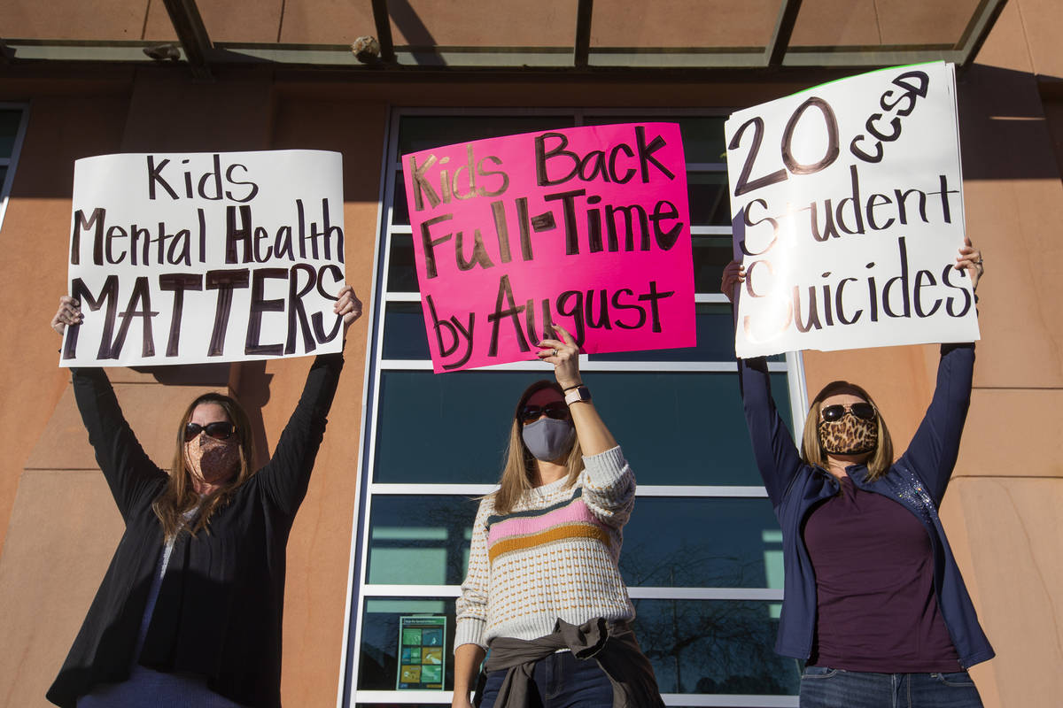Melinda Anderson, left, Julie Shipp and Brooke Watson protest for their children to go back to ...