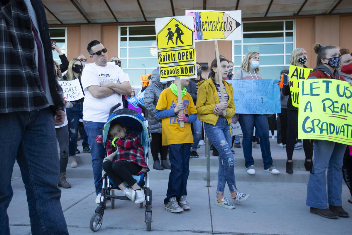 Joshua Melvin, left, and his three children Emilia, Finley and Gracie attend a protest calling ...