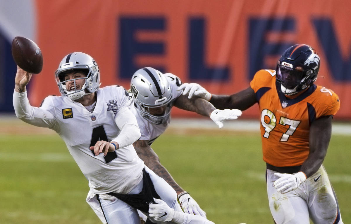 Raiders quarterback Derek Carr (4) just gets a pass away with pressure from Denver Broncos outs ...