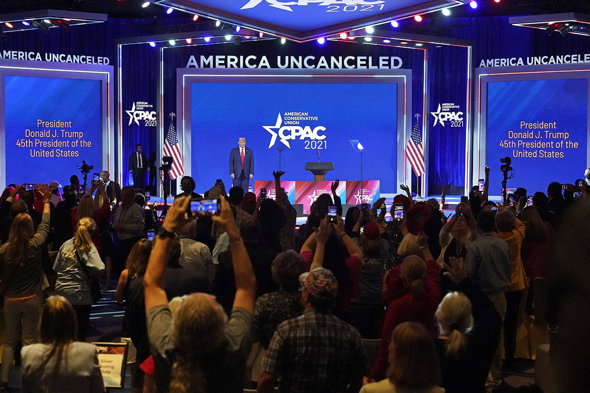Supporters cheer and wave as former president Donald Trump is introduced at the Conservative Po ...