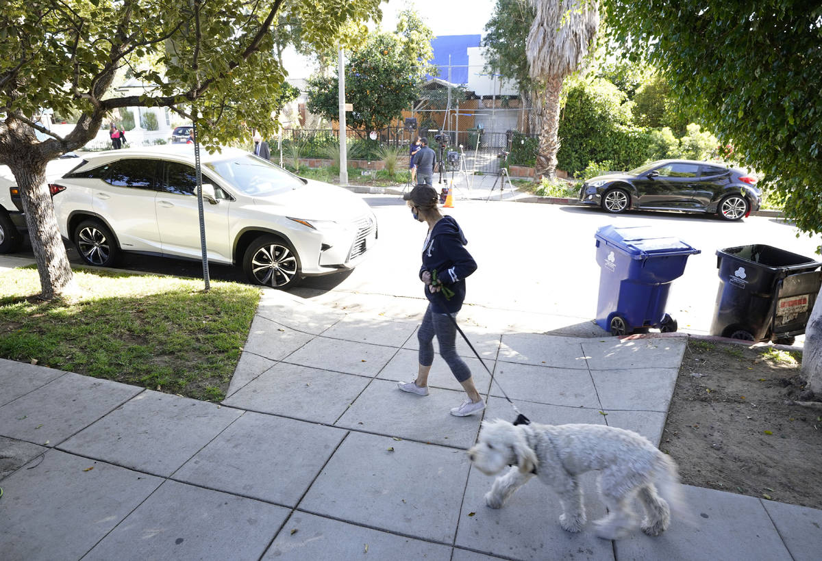 A woman walks her dog across the street from an area on North Sierra Bonita Ave. where Lady Gag ...