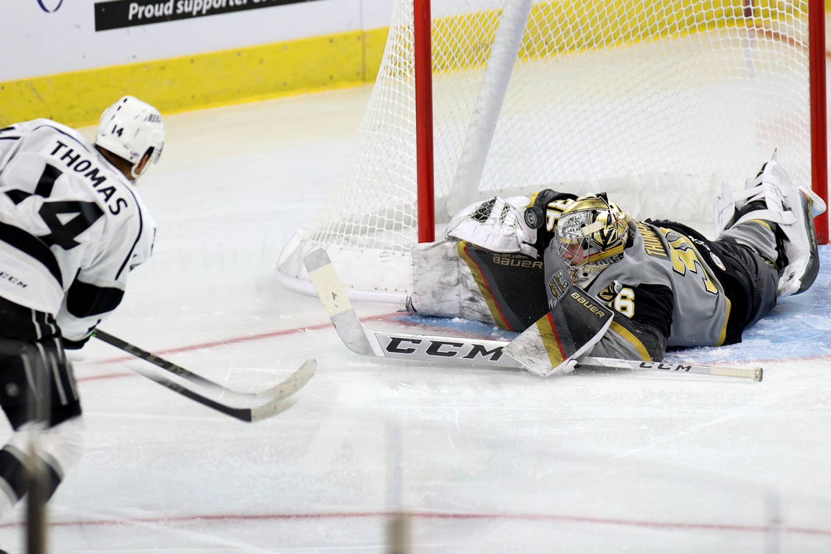Henderson Silver Knights goaltender Logan Thompson(36) blocks a shot from Ontario Reign Akil Th ...
