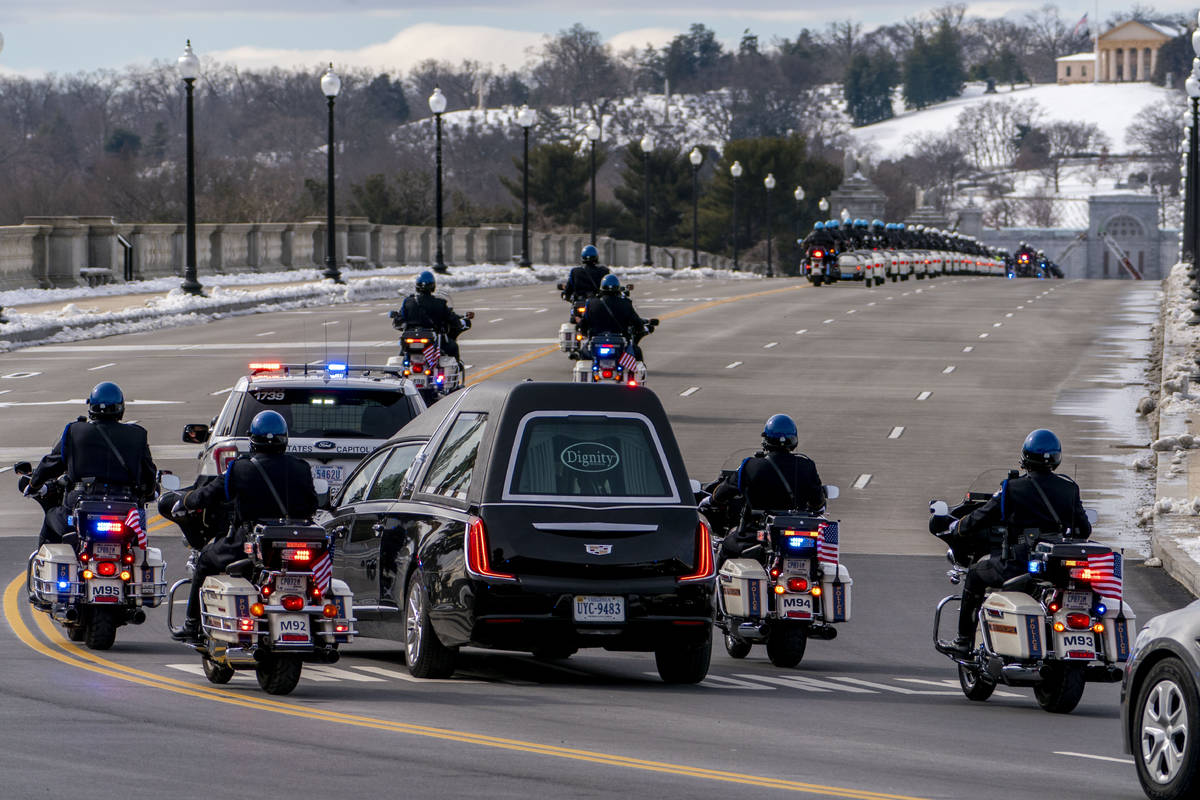 A hearse carrying the remains of U.S. Capitol Police officer Brian Sicknick makes its way to Ar ...