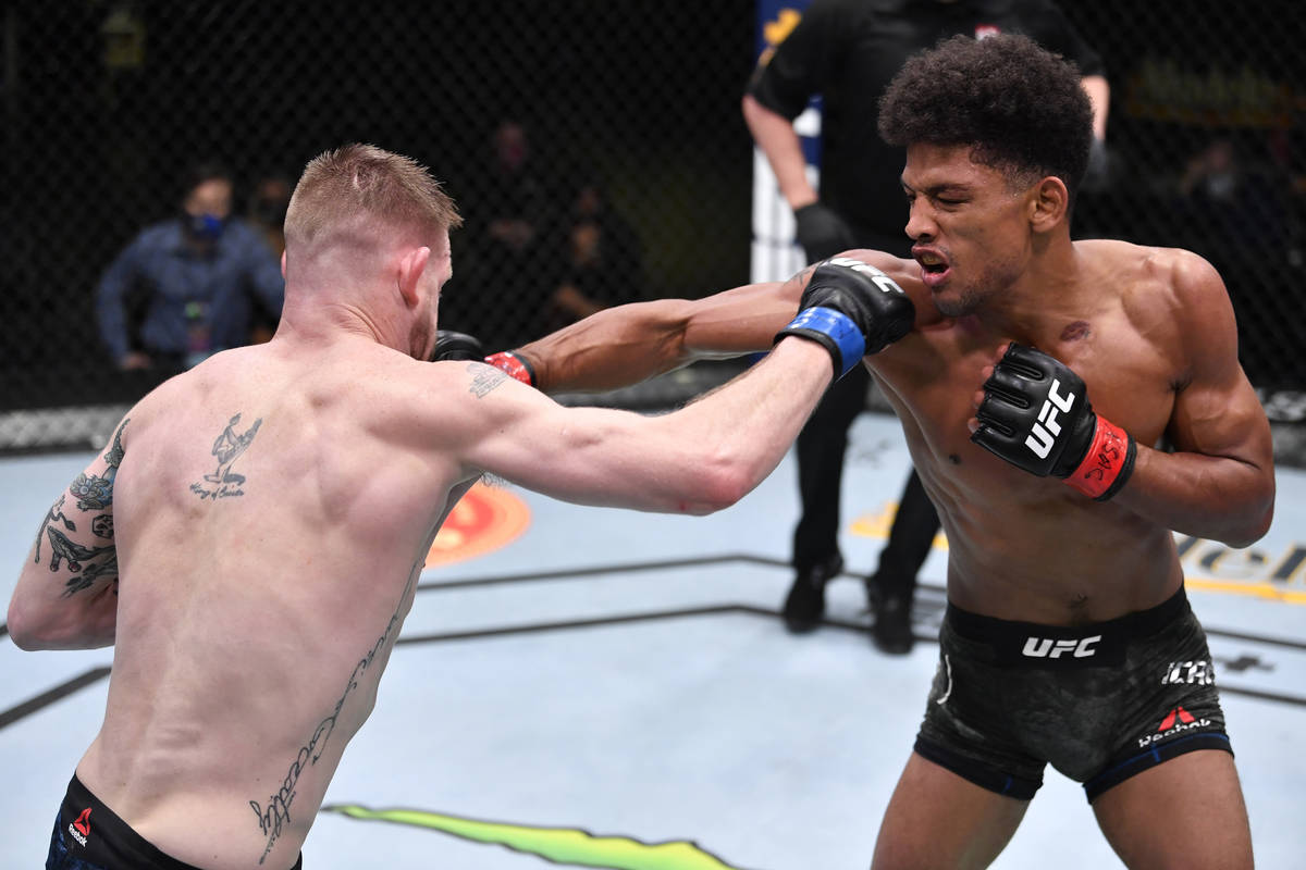 LAS VEGAS, NEVADA - FEBRUARY 27: (R-L) Alex Caceres punches Kevin Croom in a featherweight bout ...