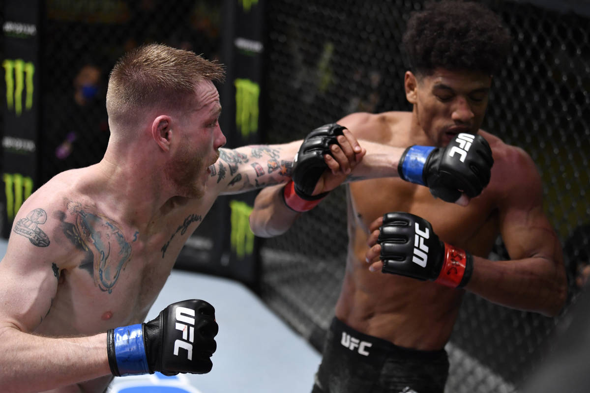 LAS VEGAS, NEVADA - FEBRUARY 27: (L-R) Kevin Croom punches Alex Caceres in a featherweight bout ...