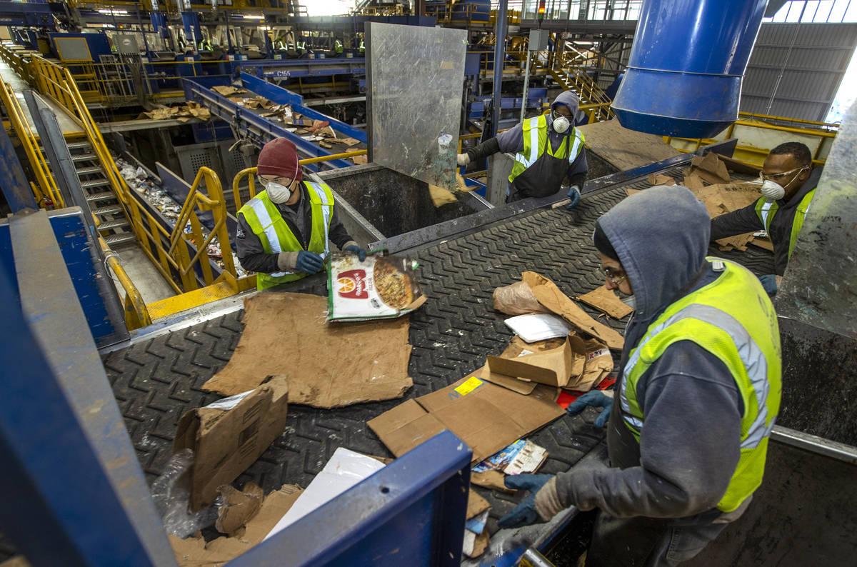 Workers sort cardboard and other fibers at the Republic Services recycling center on Jan. 15, 2 ...