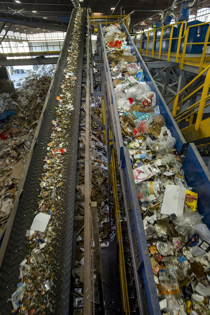 Glass, left, is sorted and moved by conveyor belt to a glass cleanup system with other material ...