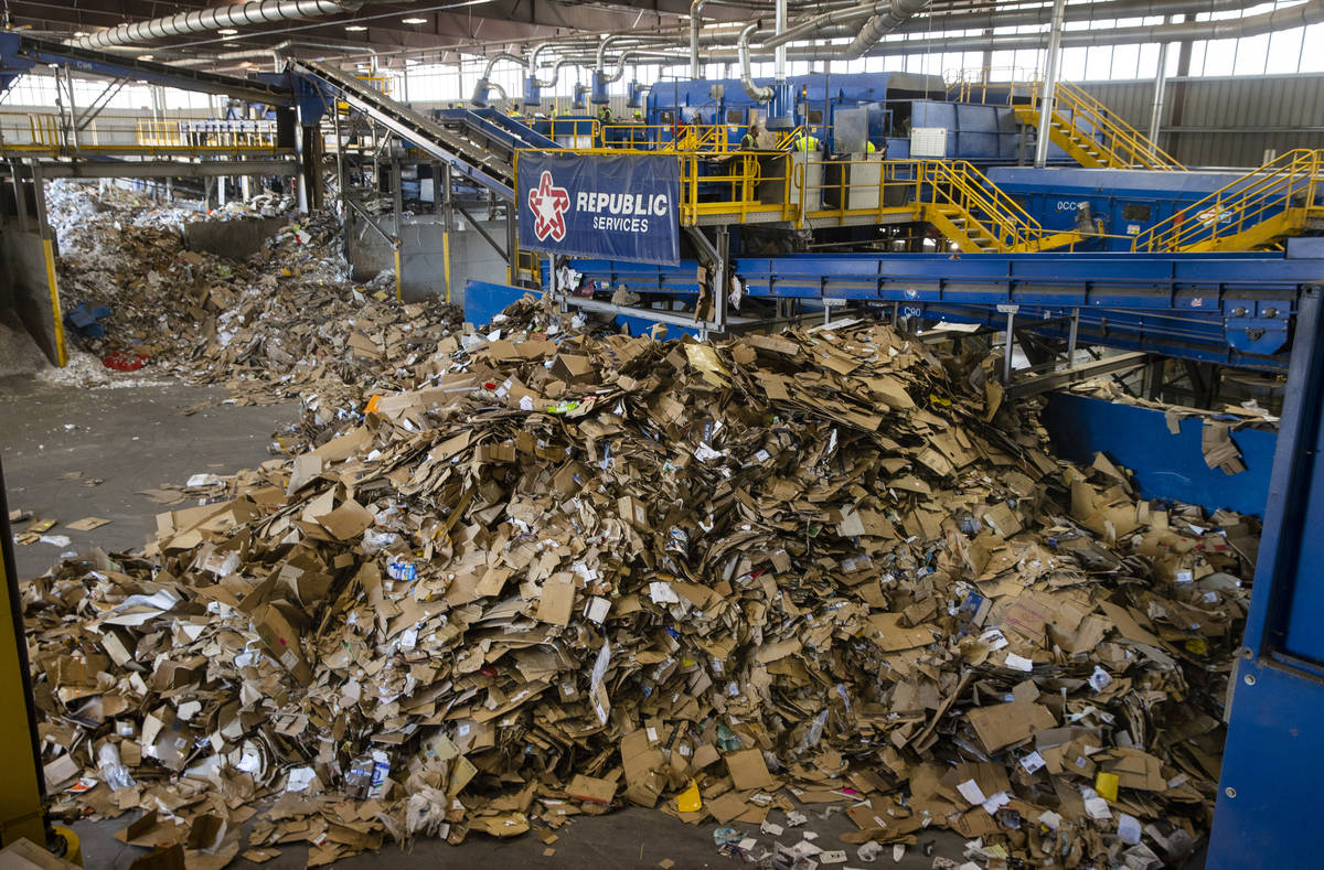 Sorted cardboard is moved down to a pile for baling as other materials continue to be sorted at ...