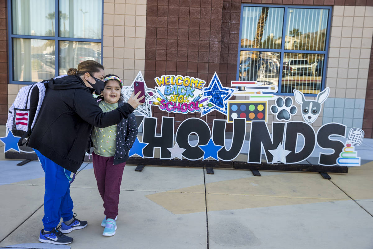 Lupe Tapia and her daughter Ariel, 8, take a photo outside of Goolsby Elementary School as she ...