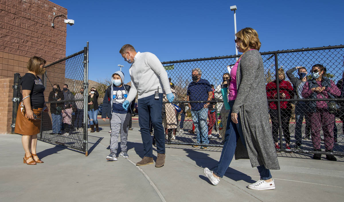 Vice principal Magdalena Casillas, from left, looks on as a student is welcomed in a side gate ...