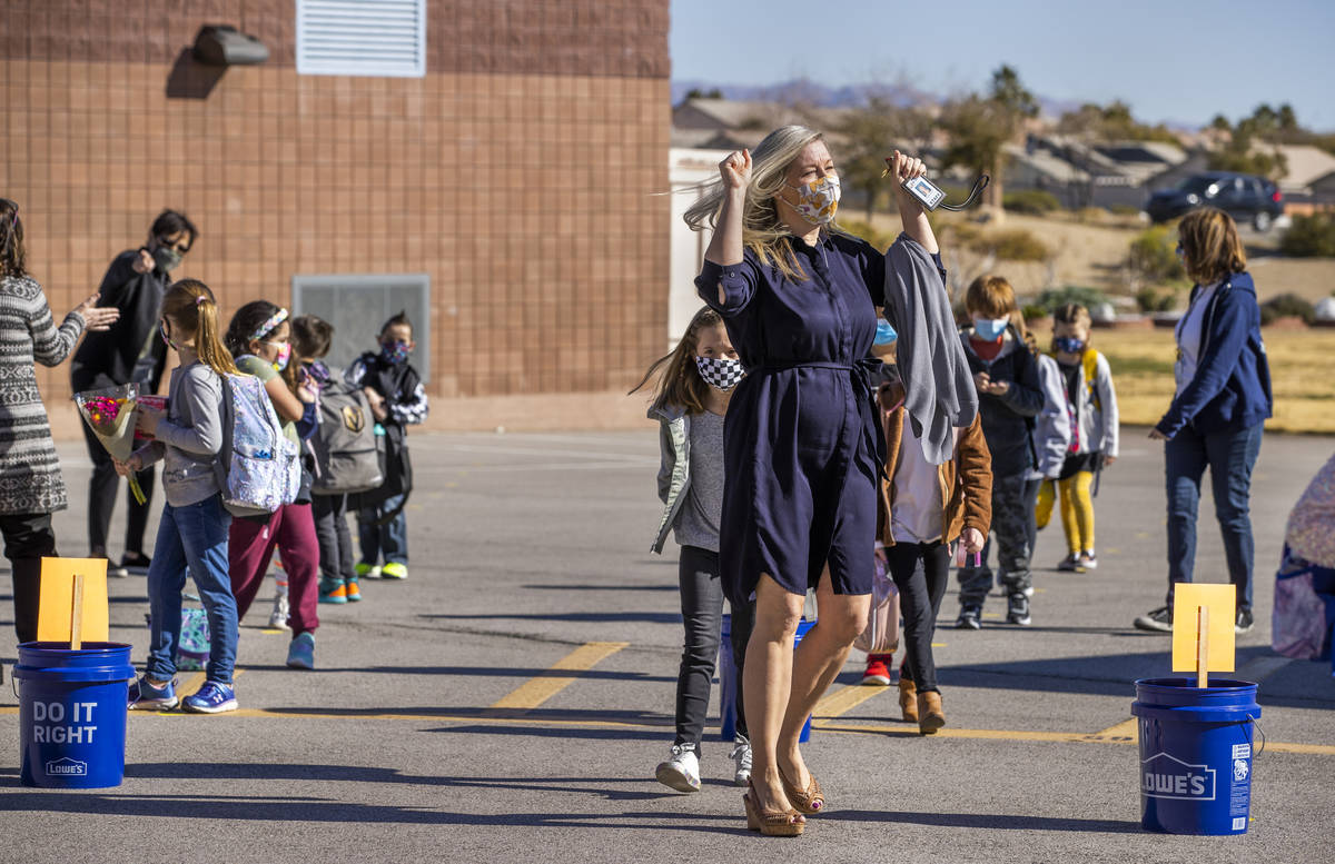 Teacher Alissa Miller is pumped up as she and other staff members lead students inside from the ...