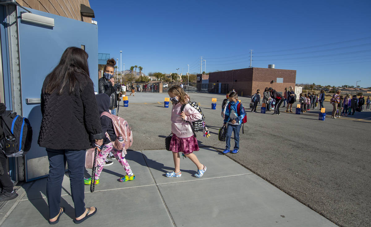 Teachers and other staff members lead students inside from the playground at Goolsby Elementary ...